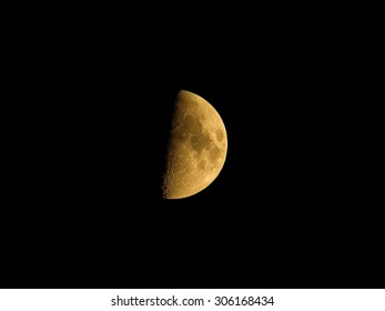 Full moon with surface details, seas and craters, in natural yellow color, isolated on black background for design.