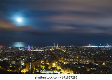 Full moon under Barcelona cityscape.
