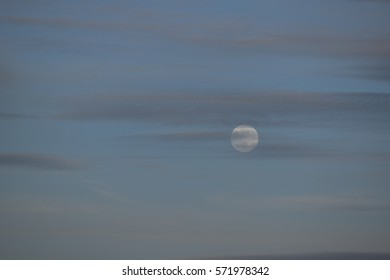 A full moon with wispy clouds.