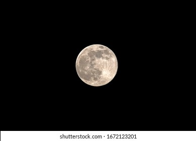 Full moon, full moon with a yellowish tinge in the night sky black. Well guilt craters of the moon.