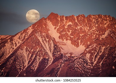 full moonset behind Basin Mountain at sunrise in the Sierra Nevada Mountains west of Bishop California