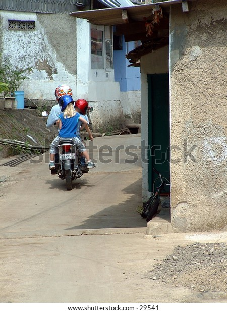 A full motorbike down a small street in Asia