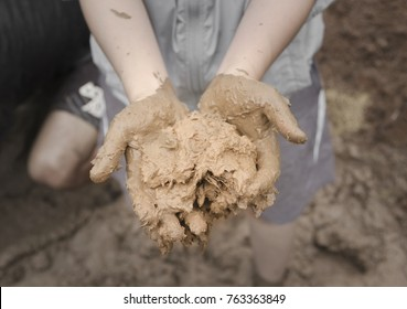 Full of mud, clay on young woman hands with lower body standing in mud pool background. Preparing mud, clay to make brick clay for built a clay house