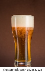 Full narrow glass of beer with foam on an orange brown background