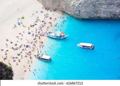 Full Navagio beach of people and three reantal boats, Shipwreck bay, Zakynthos island, Greece.