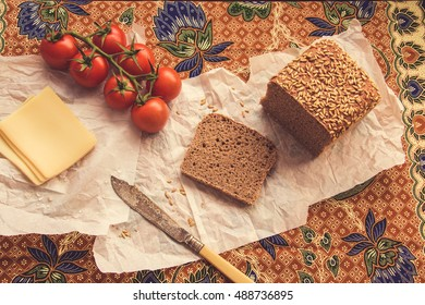 Full Oat Bread on white Paper with Cheese and Tomatoes