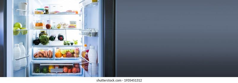 Full Open Refrigerator Or Fridge At Night In Kitchen