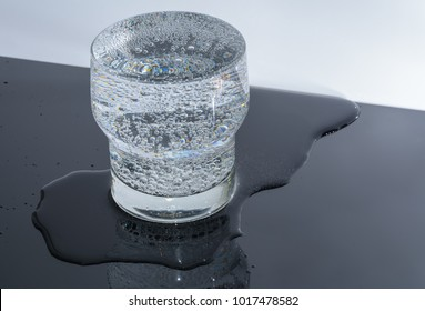 Full overflow glass with water and bubbles