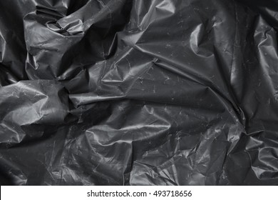 A full page of black plastic refuse sack material background texture