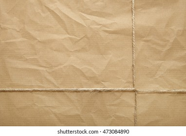 A full page of creased brown package paper texture with twine tied around it