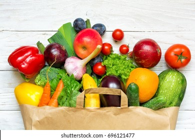 Full paper bag of different fruits and vegetables on a white wooden background. healthy food. Top view. Flat lay
