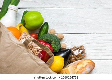 Full paper bag of different healthy vegetarian food on white wooden background. fruits, vegetables, nuts, bread and milk. Top view. Flat lay
