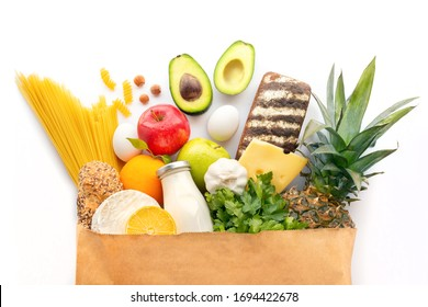 Full paper bag with healthy food.Healthy food background.Supermarket food concept.Milk, cheese, bread, fruits, vegetables, avocados, pineapple and spaghetti.Shopping at the supermarket.World food day