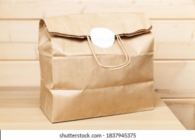 Full paper bag with white sticker stands on a table in wooden room interior