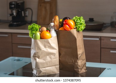 Full paper bags with food on kitchen table on dark background. Healthy and fresh eco products for a balanced diet.