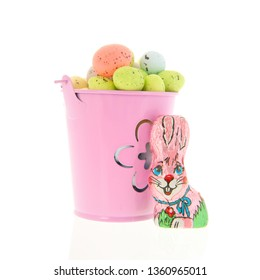 Full pastel colored easter eggs in bucket with chocolat hare isolated over white background