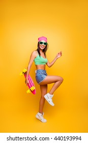 Full photo of attractive funny young hipster woman holding pink longboard and move
