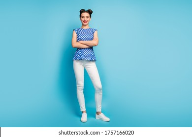 Full photo of beautiful lady good mood arms crossed enjoy weather sunny day toothy beaming smiling wear dotted blouse white pants footwear isolated blue color background