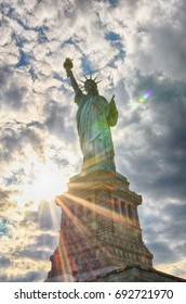 Full picture of Statue of Liberty in New York with a beautiful sky and sun rays.
