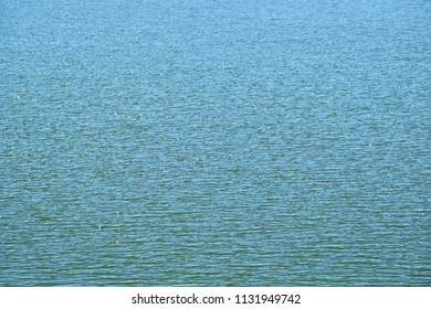 full picture of water surface with waves and sun reflections