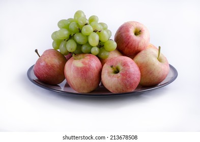 Full plate of apples and grapes on a white background.