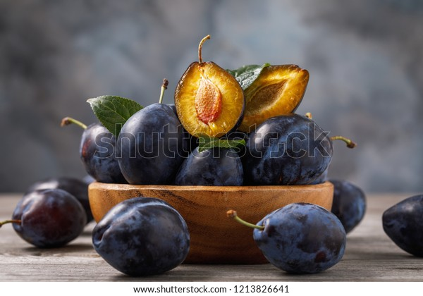 Full plate of ripe prune fruits on a wooden table, close-up