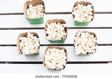 Full popcorn bowls on white wooden table from top down perspective.