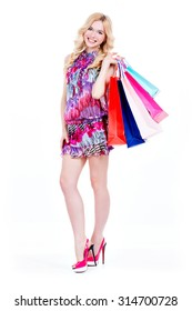 Full portrait of happy young woman with purchasing in pink dress and high heels - isolated on a white background.