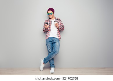 Full portrait of hipster man holding cup of coffee and typing sms.