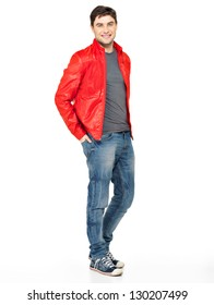 Full portrait of smiling happy handsome man in red jacket, blue jeans and gym shoes. Beautiful guy standing  isolated on white background