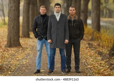 Full portrait of three friends in alley in autumn park, looking at camera