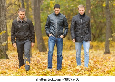 Full portrait of three friends walking in autumn park, under feet of yellow foliage