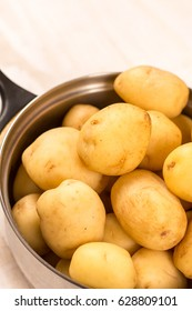 Full pot of young raw potatoes over wooden background.