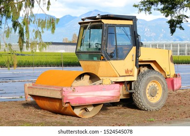Full, profile view of a used, single cab bulldozer parked near a tree farm where the industrial machine is hired to level the ground.
