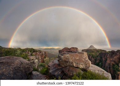 Full rainbow landscape from rocky viewpoint after rain in Karoo, South Africa.