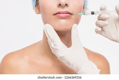 Full relaxation. Close up portrait of cosmetologist hand in gloves holding syringe near young woman face.