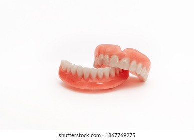 Full removable plastic denture of the jaws. Set of dentures on a white background. Two acrylic dentures. Upper and lower jaws with fake teeth. Dentures or false teeth, close-up. Copy space