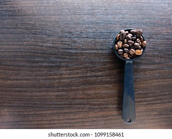Full roasted coffee beans in a black round plastic measure spoon placed on wooden background with blank space ready for texts. Shot from above or top view.