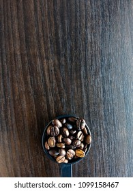 Full roasted coffee beans in a black round plastic measure spoon placed on wooden background with blank space ready for texts. Shot in vertical or portrait from above or top view.