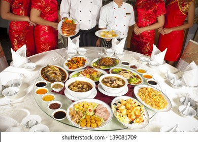 Full rounded table of Chinese food with chef and waitress behind