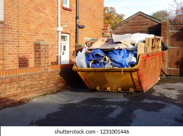 Full rubbish skip on driveway near brick wall. Big space to add text on the floor in front of the metal bin. House clearance, renovating, moving, construction building site concept.