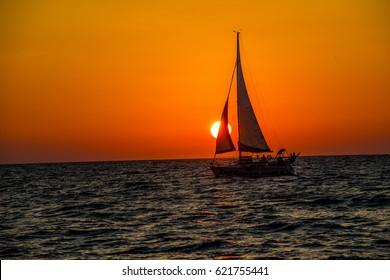 full sail sailing boat into sunset
