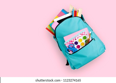 Full school backpack isolated on pink background