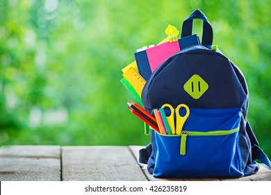 Full School backpack on wooden and nature background