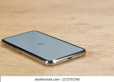 full screen Smartphone on the top of a wooden table in front of a brick wall. copy space.