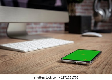 full screen Smartphone on the top of a wooden table in front of a office. Green screen for video, copy space.