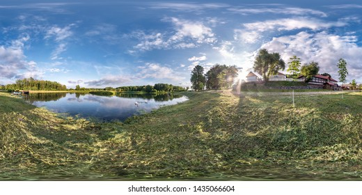 full seamless spherical hdri panorama 360 degrees angle view on grass coast of huge lake or river in summer day with beautiful clouds near the country house in equirectangular projection, VR content