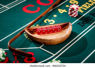 Full set of 5 dice in a wooden bowl next to the stick on a craps table with stacks of casino chip around