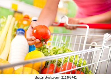 Full shopping cart at store with fresh vegetables and hands close-up.