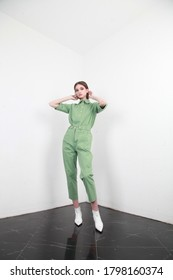 Full shot of a brown haired European lady with long hair in a summer cotton two piece suit, standing in a simple interior with white walls, studio photography, copy space - Shutterstock ID 1798160374
